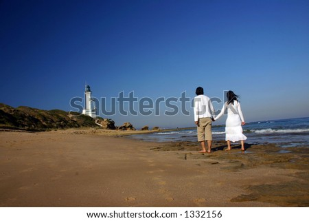 Couple at the beach holding hands walking towards the lighthouse
