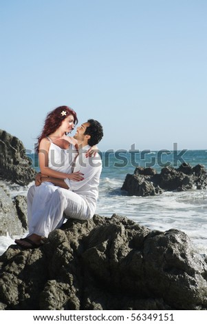 Couple at the beach sitting on rocks