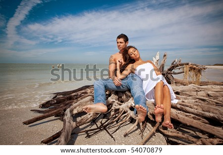 Couple at the beach, sitting on wood, relaxing