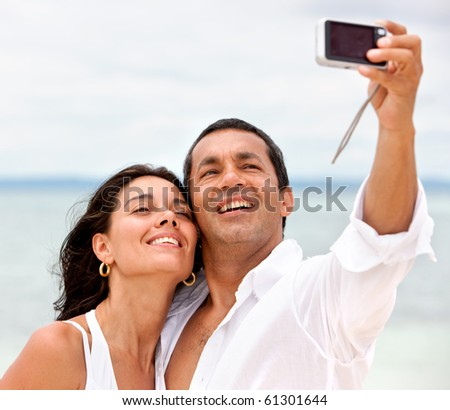 Couple at the beach smiling to the camera, taking a self portrait