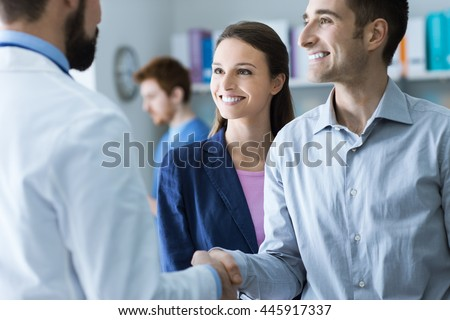 Couple at the doctor\'s office, the doctor is shaking hands with the man, healthcare and consulting concept
