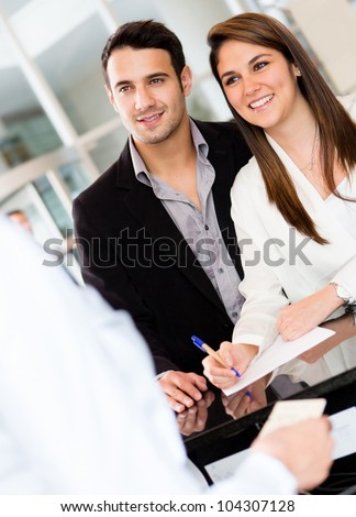Couple at the reception of a hotel smiling