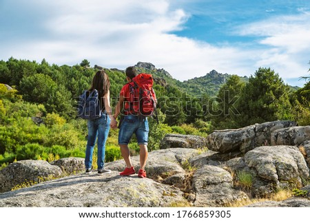 Couple back to back with backpack looking at the landscape in the mountains