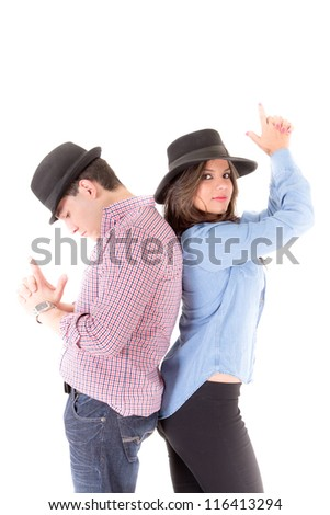 Couple back to back with hats and hands gesturing guns