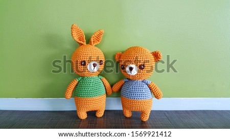 Couple bear dolls  holding hand toy knitting. Handmade Knitted Doll. Bear toy. Crochet stuffed animals. Miniature crochet Brown Bear on green Background.