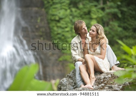 Couple being affectionate while sitting down by tropical waterfalls.