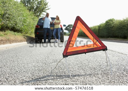 Couple Broken Down On Country Road With Hazard Warning Sign In Foreground