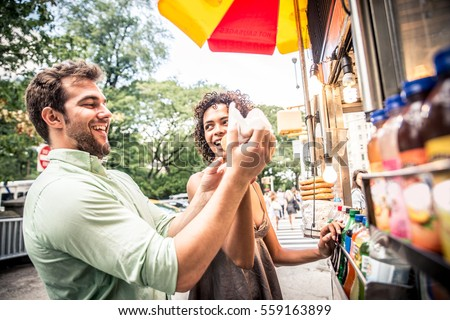 Couple buying a hot dog in a kiosk in New York #559163899