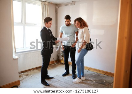 Couple Buying House For The First Time Looking At Survey With Realtor