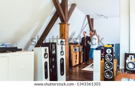 Couple buying new home stereo in Hi-Fi store with a salesman waiting