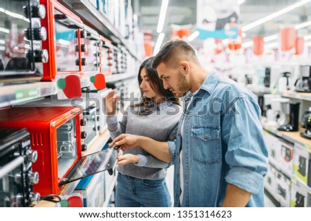 Couple buys an electric oven in a supermarket #1351314623