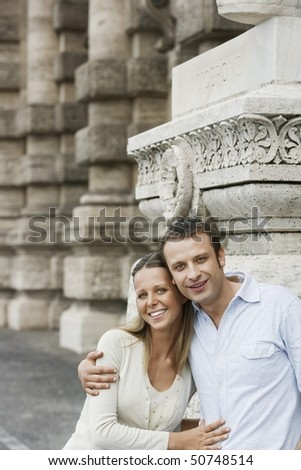 Couple by building pillars in Rome, Italy, portrait