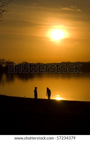 Couple by the lake at sunset