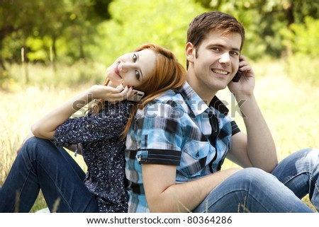 Couple calling by mobile phone at outdoor in summer time. - stock photo