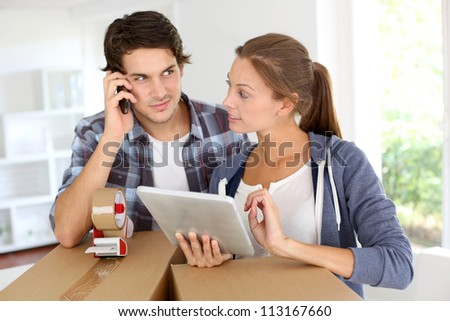 Couple calling transport company to move in new house - stock photo
