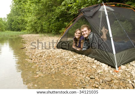Couple camping in a tent on a river bank