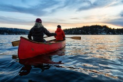 Couple canoeing on a wooden canoe in a beautiful Canadian Mountain Landscape during a vibrant winter sunset. Taken in Indian Arm, Vancouver, British Columbia, Canada.