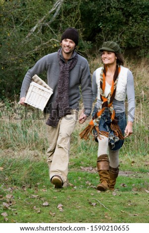 Couple carrying basket in park