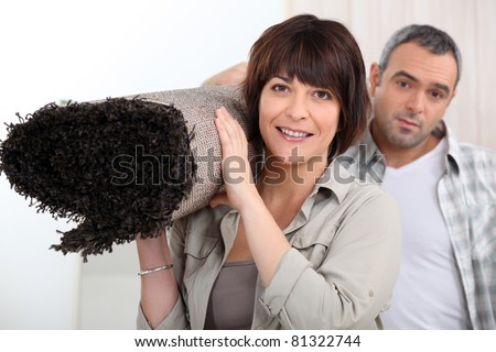 Couple carrying rug