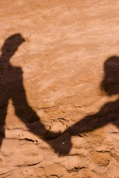Couple caught by hands in shadow on beach sand