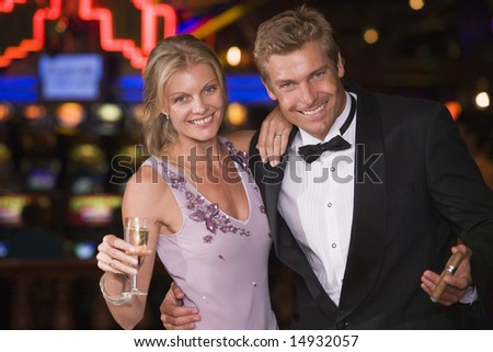 Couple celebrating inside casino with champagne