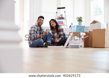Couple Celebrating Moving Into New Home With Champagne