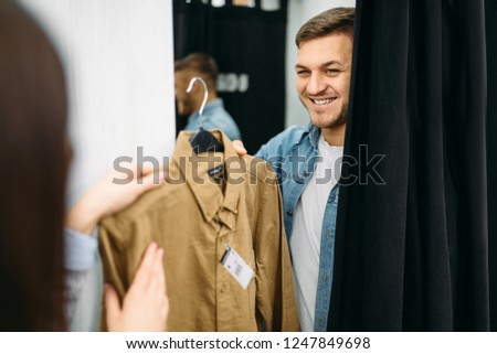Couple choosing shirts in fitting room, store