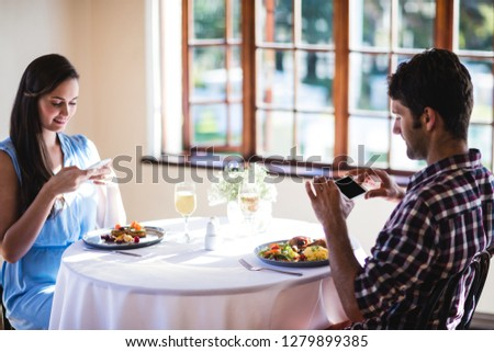 Couple clicking photo of a food on plate in restaurant