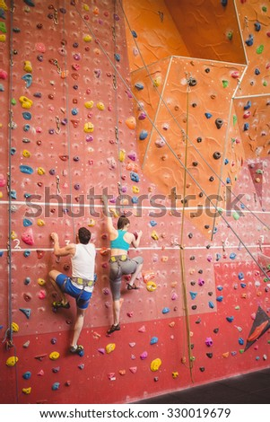 Couple climbing up rock wall at the gym