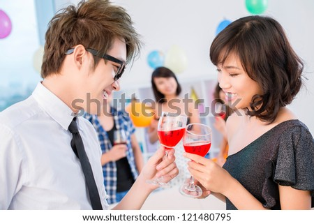 Couple clinking glasses at party