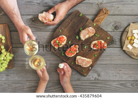 Couple clinking glasses with white wine, top view