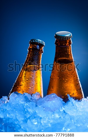 Couple cold beer bottles in ice on blue background