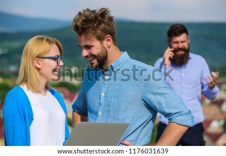 Couple colleagues flirting while boss busy with mobile conversation. Mobile internet benefits. Couple having fun while internet surfing outdoor. Colleagues use video conferencing instead mobile call. #1176031639