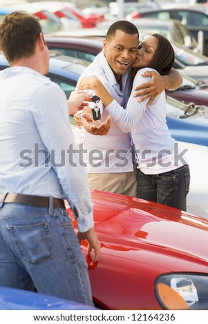 Couple collecting new car from salesman on lot