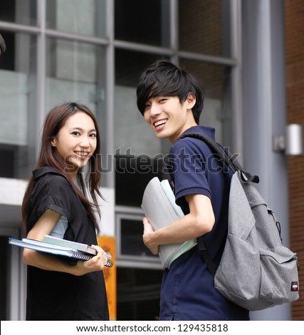 Couple college student sitting holding laptop on campus - stock photo