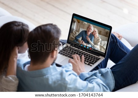 Couple communicating with elderly parents living abroad using computer and videocall application, laptop screen view over spouse shoulder. Distant virtual communication modern technology usage concept
