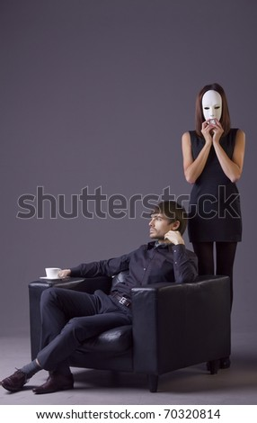 couple conflict - woman holding white mask and arrogant man with cup coffee