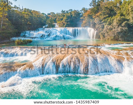 Photo of  Couple contemplating the majestic turquoise waterfalls at Agua Azul in Chiapas, Mexico
