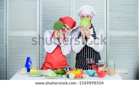 Couple cooking healthy vegetarian meal. Vegetarian family. Vegetarian nutrition and vegetable diet. Diet on their mind. Couple cooks hold cabbage and broccoli in front of face. Healthy food concept.