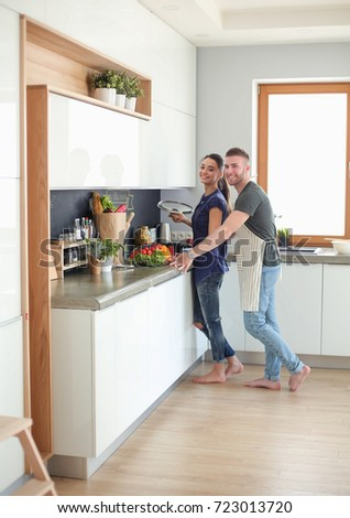 Couple cooking together in their kitchen at home - Shutterstock ID 723013720