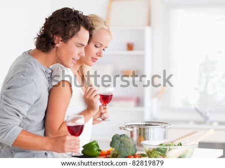 Couple cooking while having a glass of wine in their kitchen