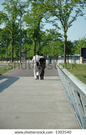 couple cuddling, leaving a bridge