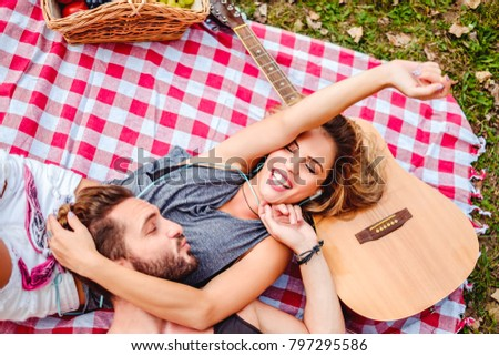 Couple Cuddling On A Picnic Blanket She Is Listening Music And He Sending Her