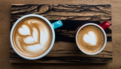 Couple cup of art latte and piccolo latte, heart graphic design on the coffee in white cup on brown wood tray