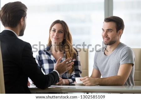 Couple customers consulting realtor lawyer or insurer about buying house or insurance services, salesman, bank worker or financial advisor making presentation offer to clients at meeting in office
