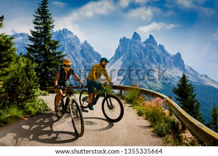 Couple cycling on electric bikes. Woman and Man riding on bikes in Dolomites mountains landscape. Cycling e-mtb trail track. Outdoor sport activity.