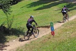 Couple cycling on mountain bike, rides mountain trail.