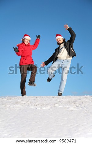 couple dance on  snow hill in santa claus hats