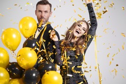 Couple dancing among falling confetti and streamer at party