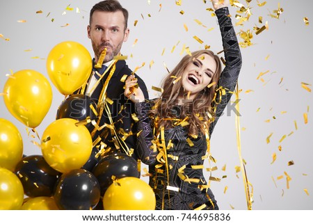 Couple dancing among falling confetti and streamer at party  #744695836